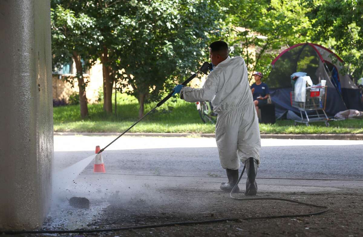 A worker power washes a Highway 59 pillar after city officials evacuated a homeless encampment due to serious health hazards under the Highway 59 overpass, between Caroline and La Branch streets Thursday, Aug. 10, 2017, in Houston. People will be able to return once the city is done with cleanup of the area. ( Godofredo A. Vasquez / Houston Chronicle )