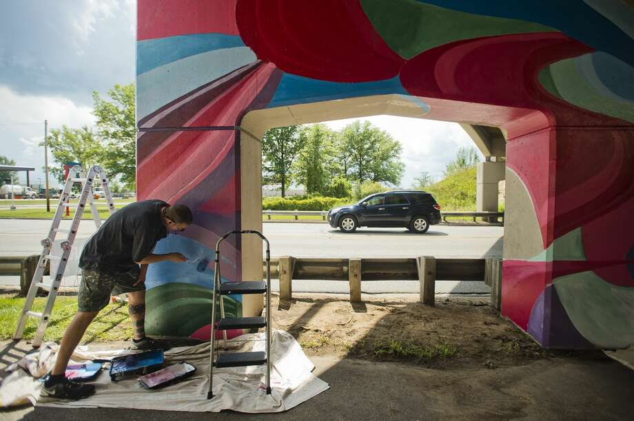 Mark Piotrowski, owner of Marked Arts, a business based in Bay City that creates murals, paints a portion of the US-10 bridge over Saginaw Road on Monday, August 7, 2017. Photo: (Katy Kildee/kkildee@mdn.net)