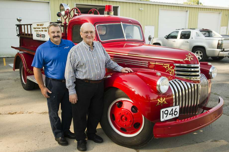 Al Kloha, right, and his son Rod Kloha, left, pose for a portrait in front of the vintage 1946 Darley firetruck Rod finished restoring as a gift to his father, on Wednesday, August 9, 2017 in Edenville. Photo: (Katy Kildee/kkildee@mdn.net)