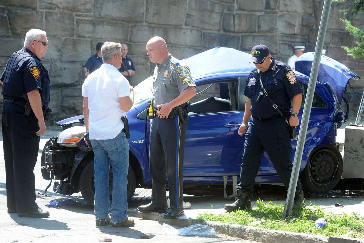 The scene at the intersection of Iranistanand Railroad avenues following a fatal accident involving a Toyota Yaris, pictured here, which was hit by another vehicle, not pictured, that was being pursued by State Police in Bridgeport, Conn. Aug. 10, 2017.