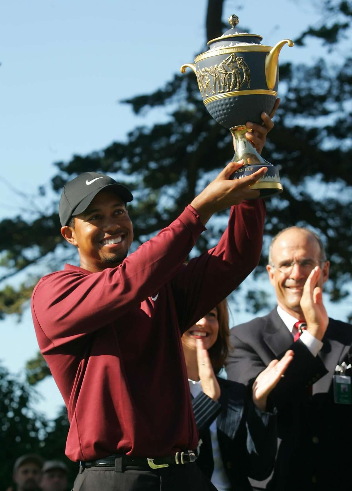 Tiger Woods holds up the trophy after winning the American Express World Golf Championships at Harding Park in San Francisco, Sunday, Oct. 9, 2005. Woods beat John Daly on the second hole of a sudden death playoff. (AP Photo/Jeff Chiu)