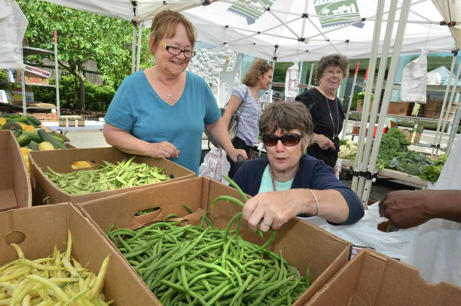 Market master for the city of Norwalk's farm stands, Lyn Detroy, helps Lisette Cimcke grab some fresh picked string beans from the Country Farms farm stand at Norwalk Community Health Center on Wednesday, July 26, in Norwalk. Cimcke is not able to use the state supplied voucher for seniors, which is being cut due to budget restraints. Photo: Alex Von Kleydorff / Hearst Connecticut Media / Norwalk Hour