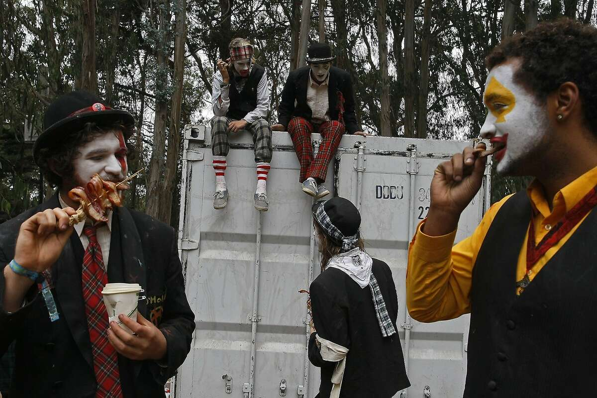 Chris Sykes, right, takes a bite of bacon while he relaxes with members of Doctor Flotsam's Hell Brew Review at Outside Lands on Saturday, Aug. 9, 2014 in San Francisco, Calif.