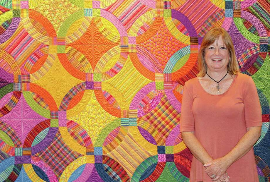 Darien resident Lisa Mason with one of her quilts which are on display in the Darien Library until Sept. Photo: Erin Kayata / Hearst Connecticut Media / Darien News