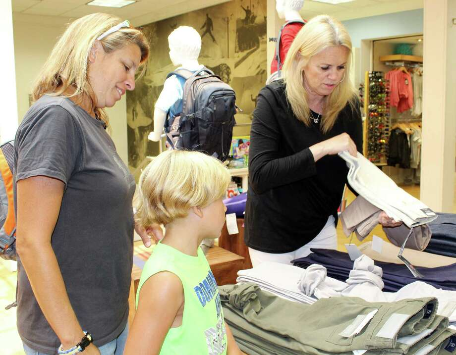 Troy Carper and mom, Meredith, pick out clothes to try on with Geri Corrigan for a back-to-school photo shoot at the Darien Sport shop in Darien. Below left, Austin Peck, 13 tries on clothes. Below right, Photo: Erin Kayata / Hearst Connecticut Media / Darien News