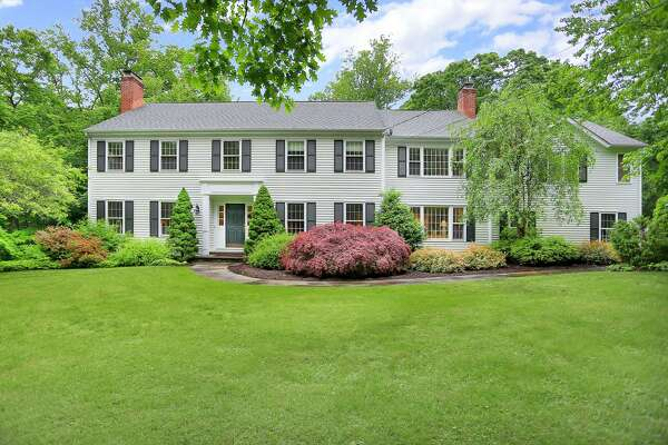 The white clapboard colonial at 312 Shrub Oak Lane sits on a 2.22-acre level property on a quiet, tree-lined cul-de-sac in northern Greenfield Hill only 1.6 miles from the Merritt Parkway.