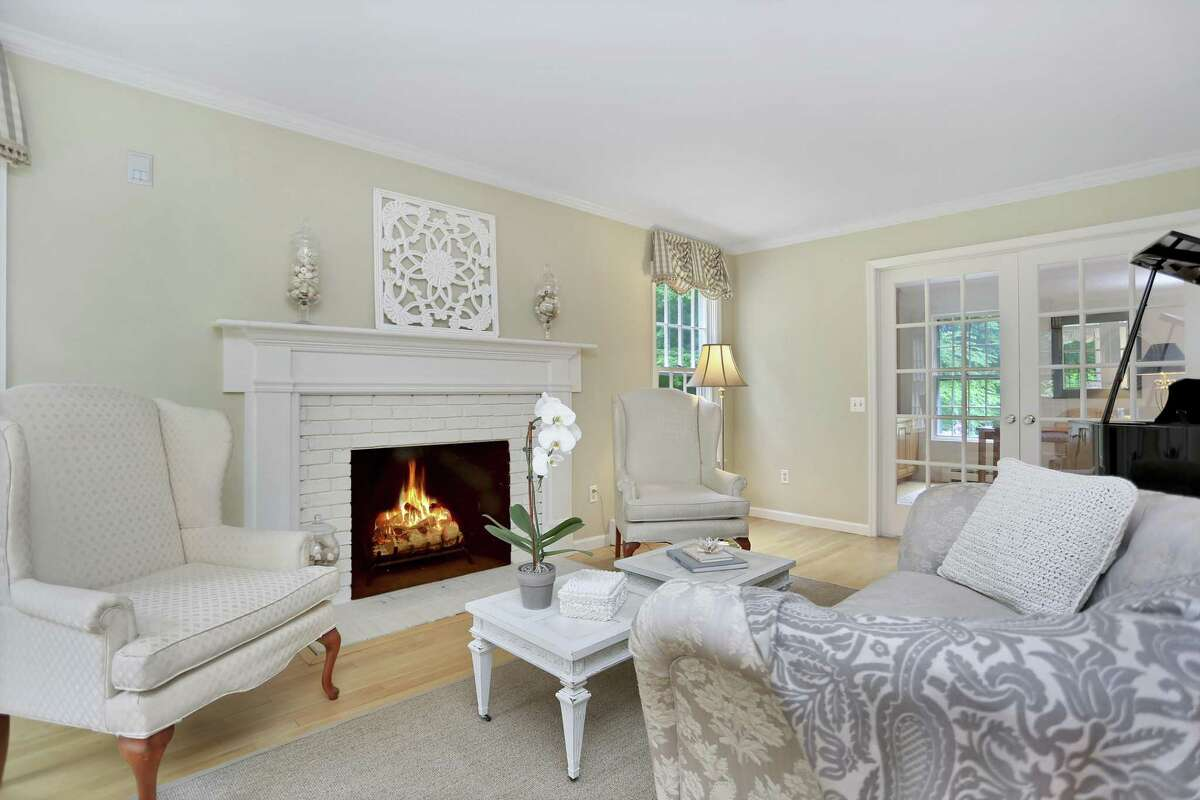 The formal living room has a fireplace and French doors that lead into the office.