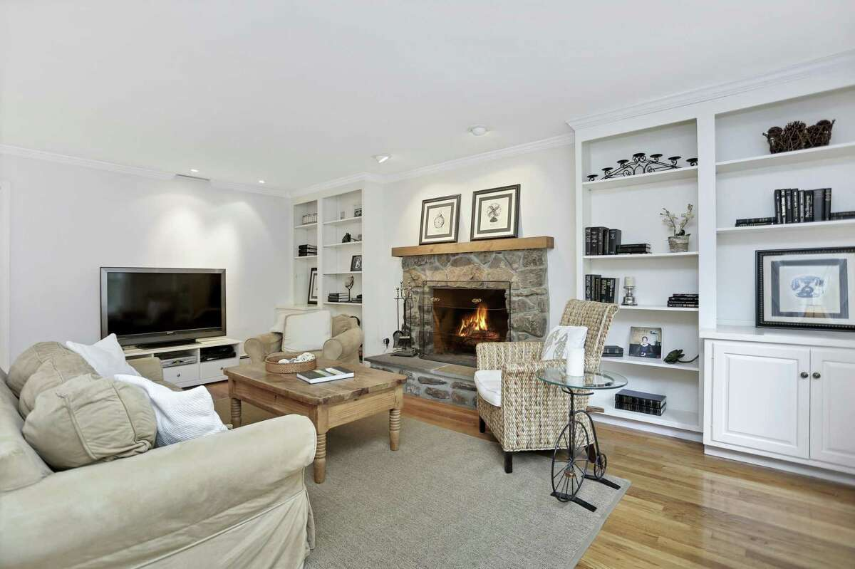 . In the family room there is a fieldstone fireplace with a raised hearth and wood mantel flanked by built-in bookshelves and lower cabinetry.