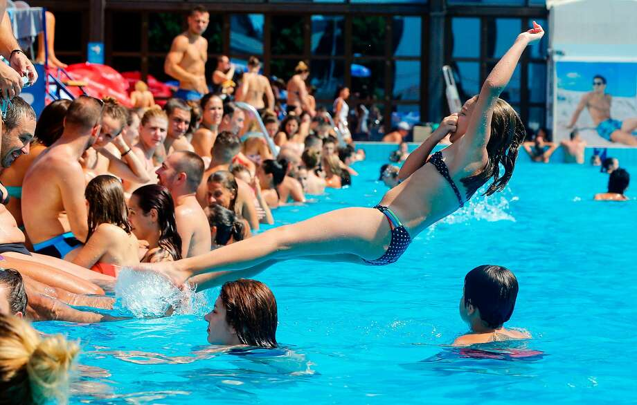 A girl jumps into a public pool in Belgrade to escape temperatures exceeding 100 degrees. Photo: PEDJA MILOSAVLJEVIC, AFP/Getty Images