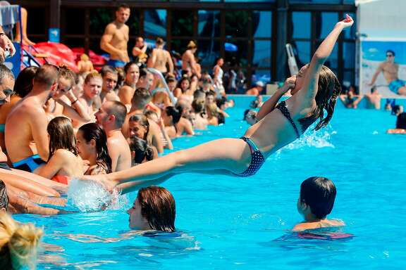 A girl jumps into a public swimming pool in Belgrade on August 5, 2017.  Southern Europe and the Balkans are experiencing a heatwave with temperatures reaching more than 40 C (104 F). / AFP PHOTO / PEDJA MILOSAVLJEVICPEDJA MILOSAVLJEVIC/AFP/Getty Images