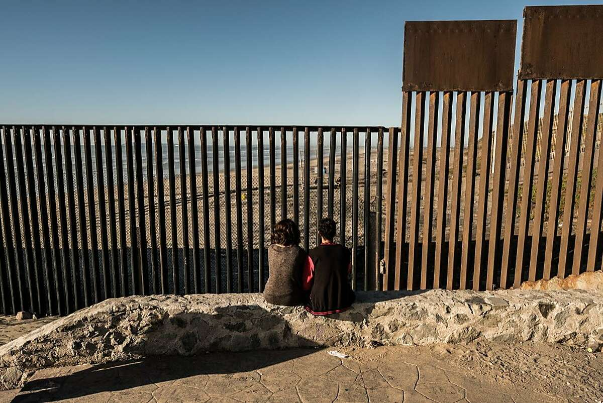 FILE � A couple sits by the border between the United States and Mexico, by the Pacific Ocean in Tijuana, Jan. 28, 2017. Though the vast majority of northbound migrants from Central America still hope to reach the United States, many are seeking to stay in Mexico, overburdening a flawed asylum system that advocates say has not kept pace with demand. (Bryan Denton/The New York Times)
