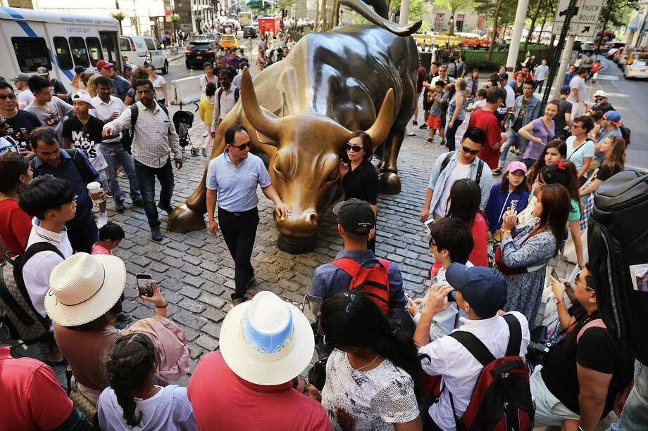 Tourists congregate in late July at the Charging Bull sculpture on Wall Street in New York City, symbolizing a bull market in finance. In a study released in early August 2017, the Securities & Exchange Commission found 2010 Dodd Frank Wall Street Reform and Consumer Protection Act did not appear to hamper the ability of companies to raise cash in the private markets. (Photo by Spencer Platt/Getty Images) Photo: Spencer Platt / Getty Images / 2017 Getty Images