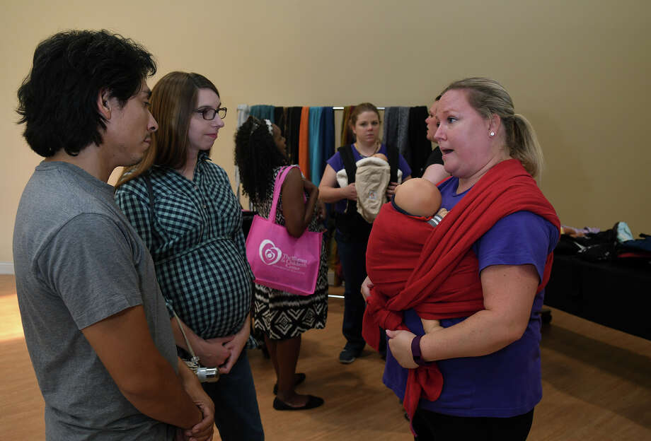 Juan Rodriguez, from left, and his wife Leah, of Atascocita, get an introduction to woven wraps from Volunteer Babywearing Educator Amanda Roberts of Babywearing International of Greater Houston during Baby Fair at the Kingwood Medical Center on August 5, 2017. (Photo by Jerry Baker/Freelance) Photo: Jerry Baker, Freelance / Freelance