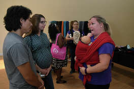 Juan Rodriguez, from left, and his wife Leah, of Atascocita, get an introduction to woven wraps from Volunteer Babywearing Educator Amanda Roberts of Babywearing International of Greater Houston during Baby Fair at the Kingwood Medical Center on August 5, 2017. (Photo by Jerry Baker/Freelance)
