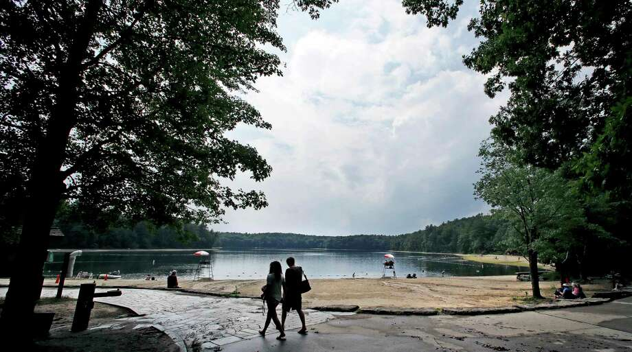FILE - In this July 12, 2017 file photo, a couple walks along the shore of Walden Pond in Concord, Mass. Two centuries after Thoreau's birth, people are still following in Thoreau's footsteps to discover Walden Pond, the little lake he immortalized, and its picturesque and historic environs. (AP Photo/Charles Krupa, File) ORG XMIT: BX307 Photo: Charles Krupa / Copyright 2017 The Associated Press. All rights reserved.