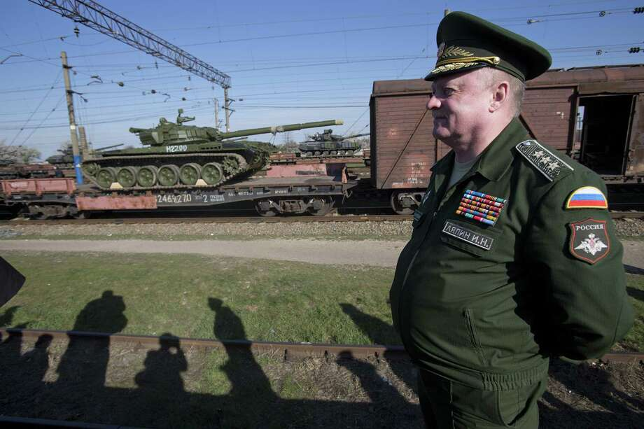 Russian head of Transport Department of the Ministry of Defense Colonel General Igor Lyapin smiles as Russian tanks T-72B, close left, arrive and Ukrainian tanks T-62, center back, are transported to the Ukraine at the Ostryakovo railway station not far from Simferopol, Crimea in 2014. Russia's annexation of Crimea should still be actively opposed by the U.S. Photo: Pavel Golovkin /AP / AP