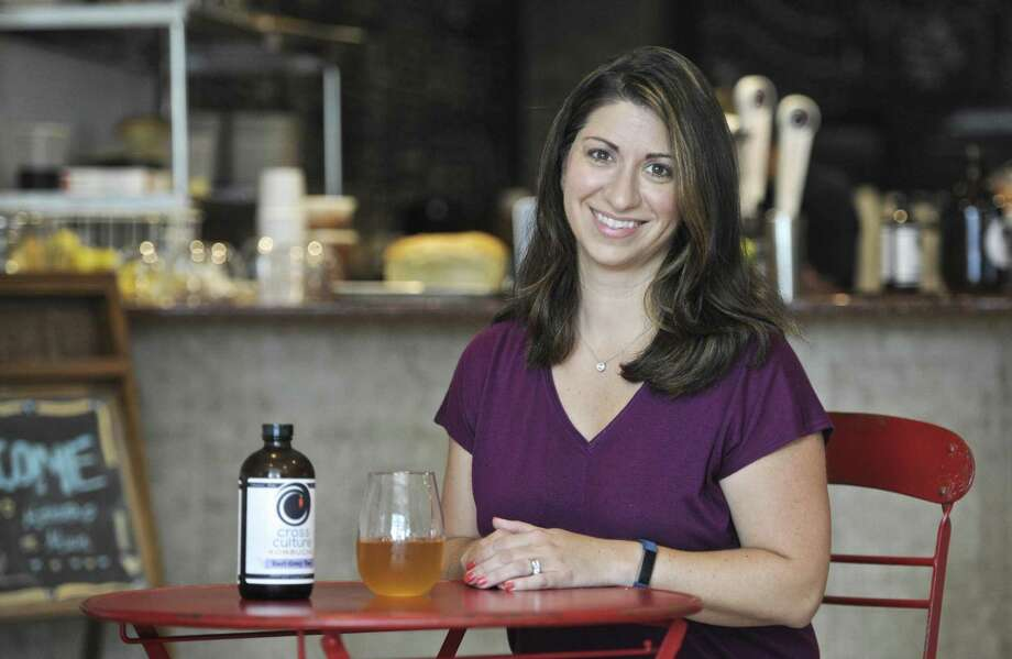 Liz Ceppos, of Danbury, co-owner of Cross Culture Kombucha sits with a glass of kombucha in Mothership On Main Thursday afternoon. August 10, 2017, in Danbury, Conn. Photo: H John Voorhees III / Hearst Connecticut Media / The News-Times