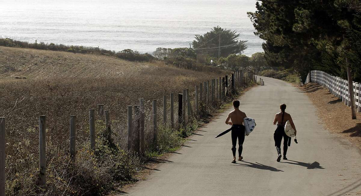Surfers Nick Nayfack, of San Francisco, left, and Taletha Derrington, right of Belmont, walk down Martin's Beach Road at Martin's Beach in San Mateo County, Calif., on Wednesday, September 24, 2014. A judge ruled on Wednesday, that property owner Vinod Khosla has to reopen the road that provides public access to the public beach.