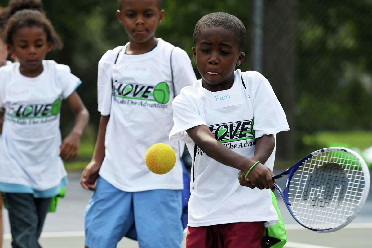 Kami Barha, 6, of Albany takes a swing at the ball during a 15-Love tennis camp at Washington Park on Thursday, Aug. 10, 2017, in Albany, N.Y. The not-for-profit youth tennis program, which serves more than 1,900 inner-city children in the cities of Albany, Troy, Schenectady and Rensselaer throughout the summer, held its 28th annual summer Jamboree. (Will Waldron/Times Union)