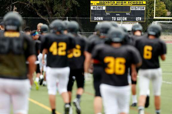 Novato High School football players head to the field for practice in Novato, Calif. on Thursday, August 3, 2017.