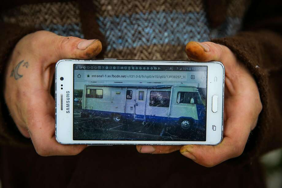 Paul Wassell shows a photo of the RV he shared with his girlfriend, Marielle Lowes, and son, Donovan Wassell, that was towed July 27. They have been homeless ever since. Photo: Gabrielle Lurie, The Chronicle