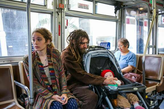 Parents Marielle Lowes (left), 24, and Paul Wassell (right) ride the bus with their son Donovan Wassell (bottom), 8-months as they make their way to a friends house in San Francisco, Calif., on Wednesday, Aug. 9, 2017. Marielle Lowes and Paul Wassell had their RV towed July 27th and have been homeless ever since.