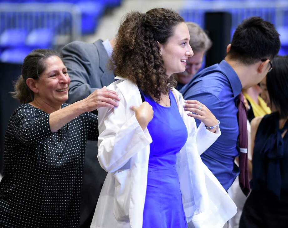 Lisa Conti (left), assistant professor of medical sciences, helps Elizabeth Cammett with her white coat during the White Coat Ceremony for students in the Frank H. Netter MD School of Medicine at the Quinnipiac Sports Center in Hamden on 8/10/2017.  Arnold Gold / Hearst Connecticut Media Photo: Arnold Gold, Hearst Connecticut Media / New Haven Register