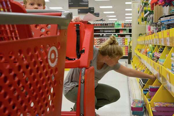 Stephanie Randall goes through school supplies while doing back to school shopping with her three-year-old son, Preston, at a Target store Thursday, Aug. 10, 2017, in Houston. Preston will go to three-year-old preschool this year. ( Yi-Chin Lee / Houston Chronicle )