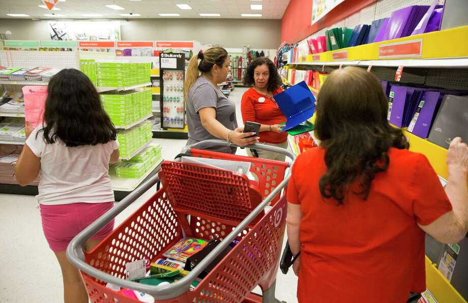 Target store team leader Beatriz Castaneda, center in red, and team member Sulema Valdez help Nelly Olivares look for folders Thursday in Houston. Photo: Yi-Chin Lee, Staff / © 2017  Houston Chronicle