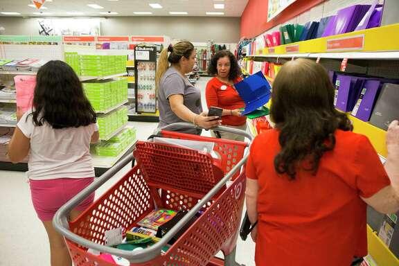 Target store team leader Beatriz Castaneda, center in red, and team member Sulema Valdez help Nelly Olivares look for folders Thursday in Houston.