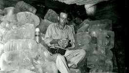 Willie Shannon eats his lunch in an ice house during a heat wave in June 1948.