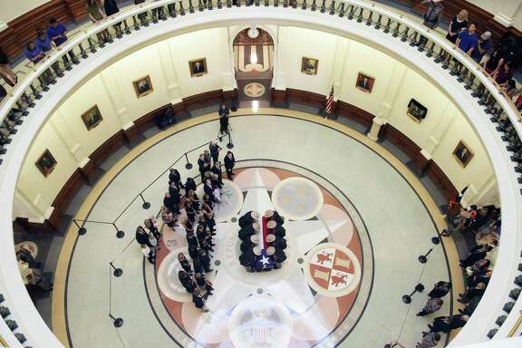 Troopers carry the casket as hundreds of people stream through the rotunda of the State Capitol to pay last respects to Governor Mark White on August 10, 2017.