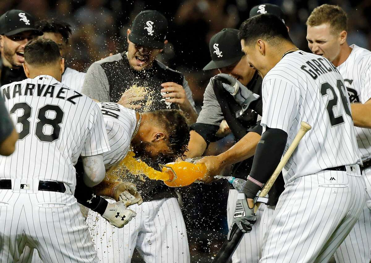 CHICAGO, IL - AUGUST 10: Yoan Moncada #10 of the Chicago White Sox is mobbed by teammates after hitting a walkoff RBI single against the Houston Astros at Guaranteed Rate Field on August 10, 2017 in Chicago, Illinois. The Chicago White Sox won 3-2 in eleven innings. (Photo by Jon Durr/Getty Images)