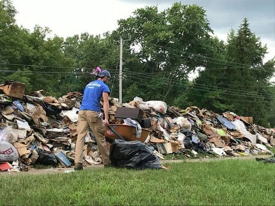 A NECHAMA-Jewish Response to Disaster volunteer helpsalocalflood victim clean up from the late June flood.