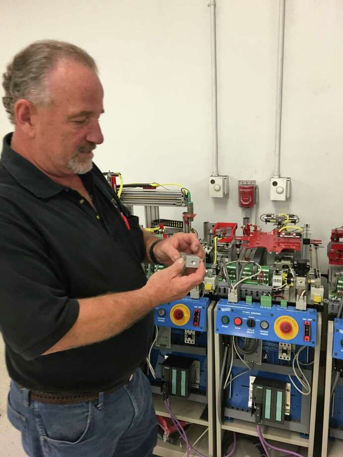 Mike Branch, the lead mechatronics instructor at Houston's Lone Star College, explains the equipment used to train students for advanced manufacturing jobs.  Photo: Chris Tomlinson