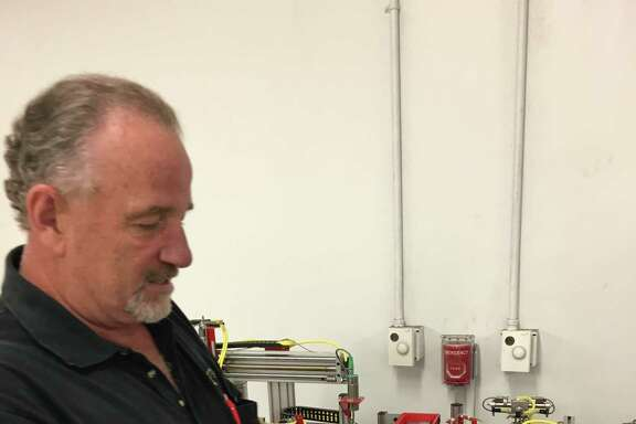 Mike Branch, lead mechatronics instructor at Lone Star College, explains the equipment used to train students for advanced manufacturing jobs. Students learn basic electronics, pneumatics, hydraulics and other areas.