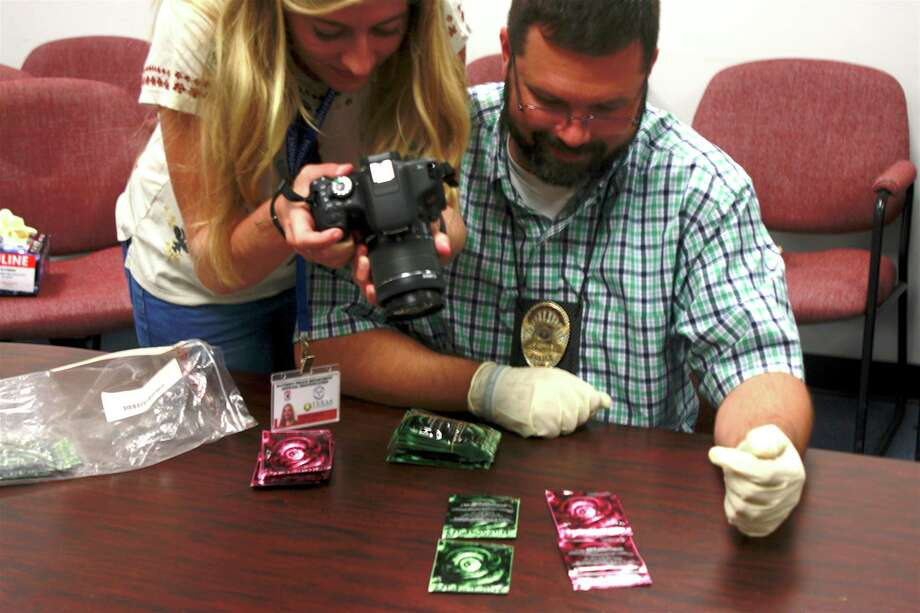 "Detective Aaron Crowell of the Baytown Police Department holds up synthetic marijuana packing for Audrey Mesler to photograph for ""The Last High"" documentary. Photo: Aaron Crowell"