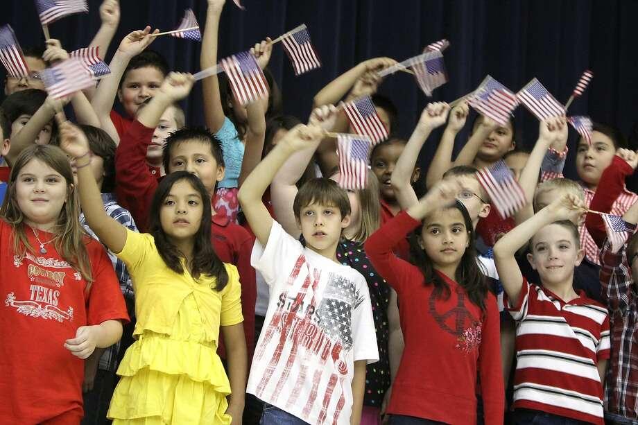 Third-graders wave American flags in Katy, Texas. Photo: Alan Warren, Houston Community Newspapers