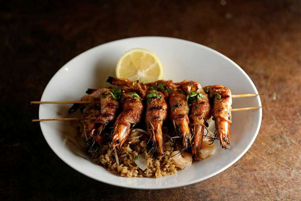 The Trung Sisters: shrimp wrapped with Thai basil, onions and bacon served over shrimp fried rice topped with lemon butter at Maba Pan-Asian Diner