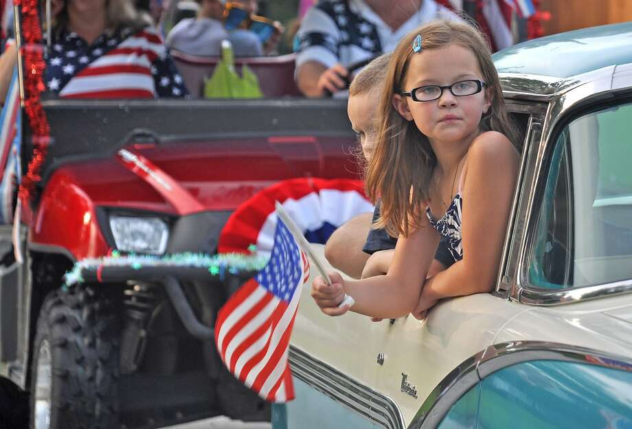 A young girl waves an American flag in as she peers out the window of a classic car in Oak Ridge, Texas. Photo: Kendra Berglund, Photo By Kendra Berglund