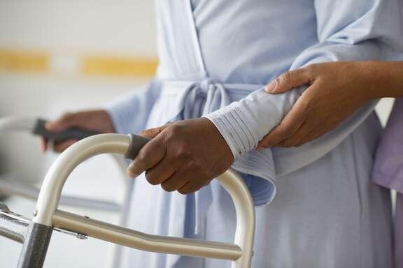 Nurse helping woman use walker in hospital hallway Details Credit: Blend Images - JGI/Tom Grill