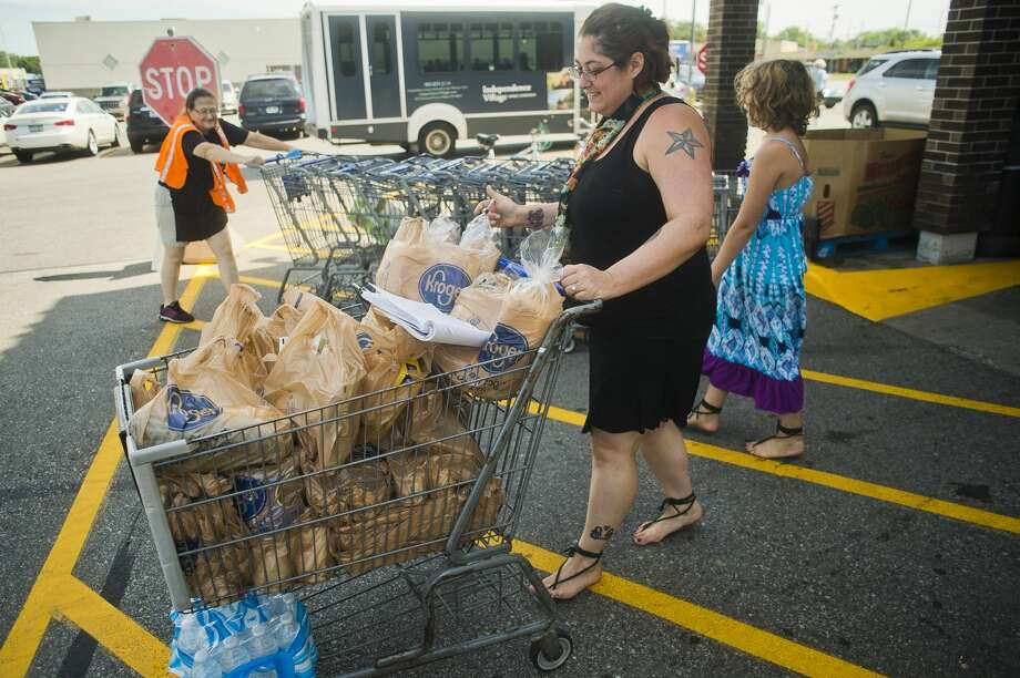 Billie MacDonald, center, and her daughter, Angellicka, 9, right, exit Kroger after stocking up on groceries on Thursday, July 20, 2017 in Midland. Photo: (Katy Kildee/kkildee@mdn.net)