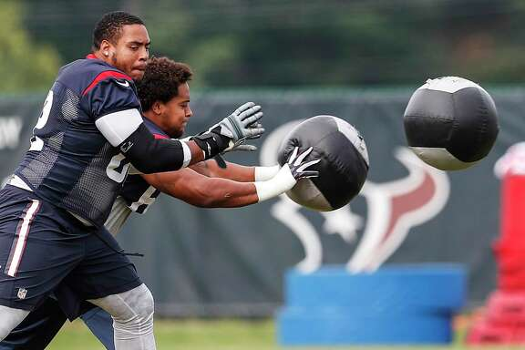 Houston Texans guard Chad Slade, left, and tackle Kendall Lamm throw around the medicine ball during training camp at The Greenbrier on Friday, Aug. 11, 2017, in White Sulphur Springs, W.Va.