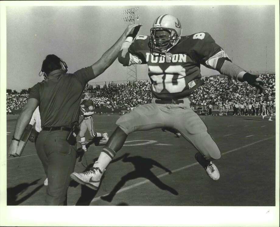 Judson High School Football Player High Fives Coach on Field / San Antonio Express-News