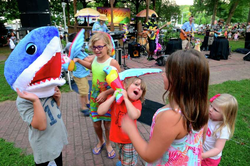 Silas Mokay, 4, of Shelton, center, plays with his sister Hannah, 10, in back, and other relatives as the Jimmy Buffet tribute band Parrotbeach performs during Shelton Parks and Recreation's 2017 Music Under the Stars concert series on Huntington Green in Shelton, Conn. on Wednesday August 9, 2017. The next concert is August 16 - Terrapin Grateful Dead from 7 p.m. to 9 p.m..