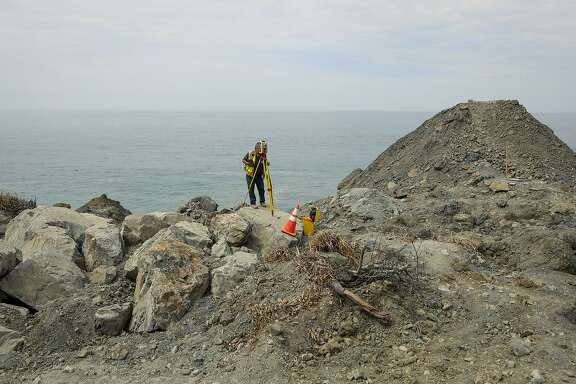 Bob Brown, with Caltrans, monitors boulders for movement high up on the Mud Creek slide near Gorda, Calif., Thursday, Aug. 3, 2017. California officials say they'll build a road over the massive Central Coast landslide that closed the scenic coastal highway leading to Big Sur. The Department of Transportation announced Tuesday that spanning the Mud Creek site will be a faster and cheaper way of reopening Highway 1, compared to boring a tunnel or sidestepping the slide area. (Joe Johnston /The Tribune (of San Luis Obispo) via AP)