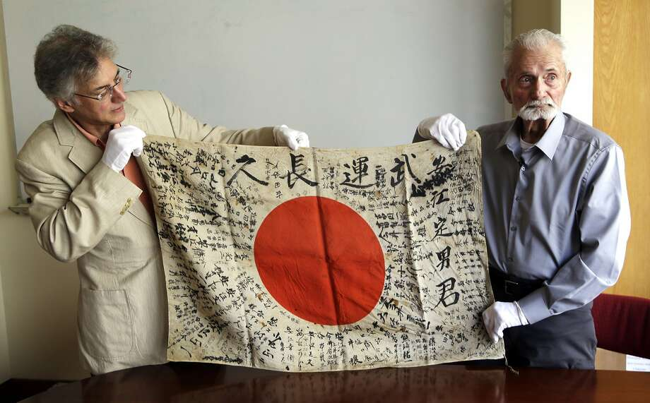 Obon Society co-founder Rex Ziak (left) and World War II vet Marvin Strombo display the bat tlefield flag Strombo took from a dead Japanese soldier in the Pacific more than 70 years ago. Photo: Don Ryan, Associated Press