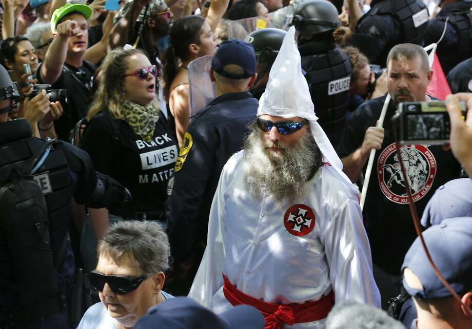 This July 8, 2017 photo shows members of the KKK escorted by police past a large group of protesters during a KKK rally in Charlottesville, Va.  Some white Southerners are again advocating for what the Confederacy tried and failed to do in the 1860s: secession from the Union. So-called Southern nationalists are within the group of demonstrators who are fighting the removal of Confederate monuments around the South. They say it's time for Southern states to secede again and become independent of the United States..(AP Photo/Steve Helber) Photo: Steve Helber, Associated Press