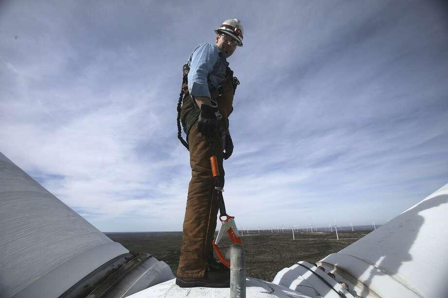 Randy Adams hangs off the hub of a wind turbine prop at the Desert Sky Wind Farm. Adams was performing maintenance on one of the aging wind turbines that supply power to CPS Energy. Photo: John Davenport / San Antonio Express-News / ©San Antonio Express-News/John Davenport