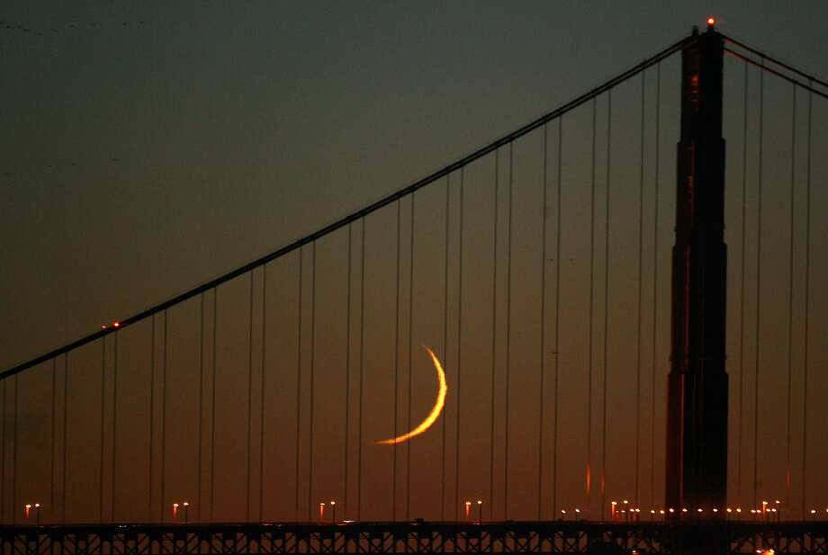 In this file photo, a thin crescent moon finds a resting spot during the evening twilight between the cables near the south tower of the Golden Gate Bridge, which was viewed from Fisherman Wharf. Photo: Frederic Larson, SFC